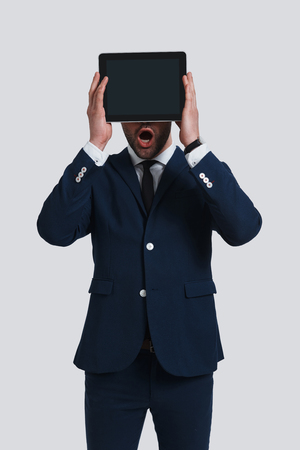 Real surprise. Shocked young man in full suit covering face with digital tablet and keeping mouth open while standing against grey background