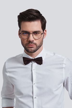 Portrait of elegance and charisma. Good looking young man in eyewear looking at camera while standing against grey background 스톡 콘텐츠