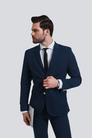 Used to look perfect. Good looking young man in full suit adjusting his jacket and looking away while standing against grey background Banque d'images