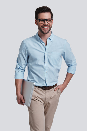 Happy man.  Good looking young man carrying laptop and looking away with smile while standing against grey background