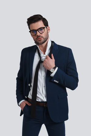 Feeling exhausted.  Exhausted young man in full suit looking at camera and taking off his necktie while standing against grey background Banque d'images