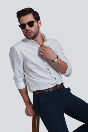 He got the look. Good looking young man in eyewear looking away while sitting against grey background