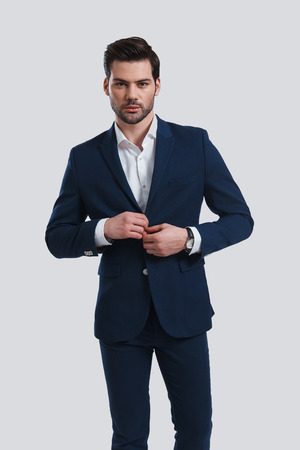 Confident in his style. Handsome young man in full suit adjusting his jacket and looking at camera while standing against grey background