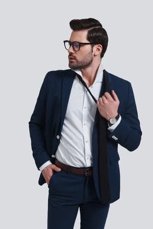 Feeling tired.  Exhausted young man in full suit looking away and taking off his necktie while standing against grey background