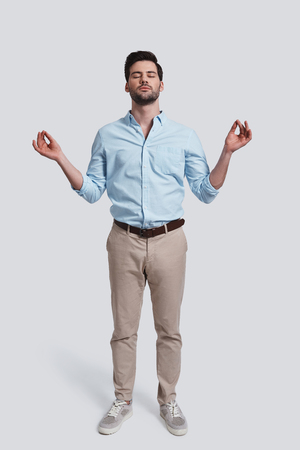 Just relaxing.  Full length of handsome young man meditating and keeping eyes closed while standing against grey background