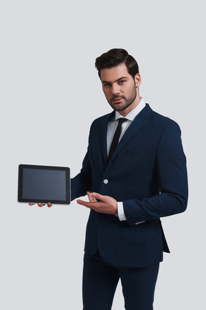 Look over here. Good looking young man in full suit pointing at digital tablet and looking at camera while standing against grey background