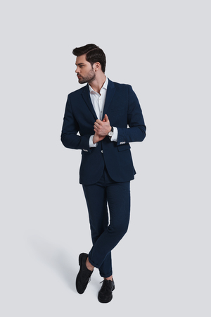 Perfect style. Full length of handsome young man in full suit looking away and keeping hands clasped while standing against grey background