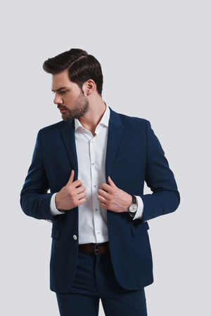 Confidence and charisma. Handsome young man in full suit adjusting his jacket and looking away while standing against grey background