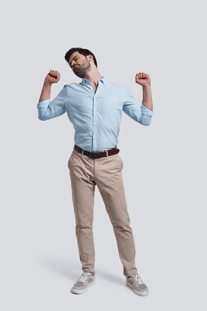 So tired.  Full length of handsome young man stretching while standing against grey background