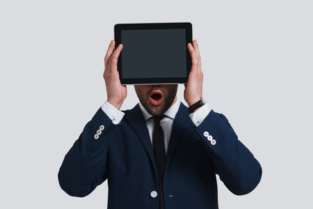 No way! Shocked young man in full suit covering face with digital tablet and keeping mouth open while standing against grey background Banque d'images