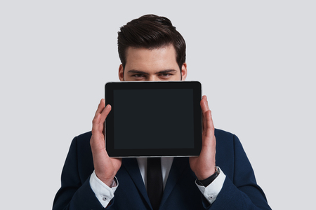 Using modern technologies. Good looking young man in full suit holding digital tablet and looking at camera while standing against grey background