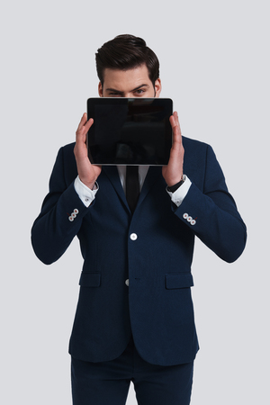 Confident business expert. Good looking young man in full suit holding digital tablet and looking at camera while standing against grey background