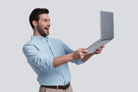 Feeling happy.  Good looking young man holding his laptop and smiling while standing against grey background
