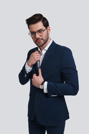 He got great style. Handsome young man in full suit adjusting his jacket and looking at camera with smile while standing against grey background Banque d'images