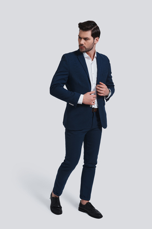Used to look perfect. Full length of handsome young man in full suit looking away and adjusting his jacket while standing against grey background