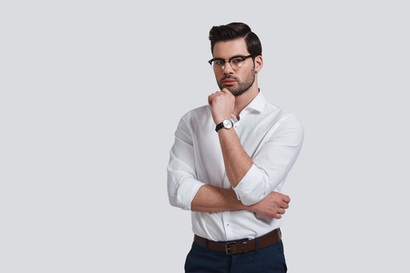 Hard choice. Good looking young man in formalwear keeping hand on chin and looking at camera while standing against grey background Banque d'images