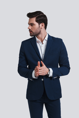 Young and successful. Handsome young man in full suit keeping hands clasped and looking away while standing against grey background