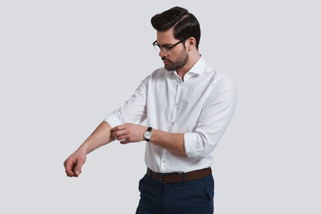 Taking everything seriously. Good looking young man in formalwear adjusting his sleeve while standing against grey background Banque d'images