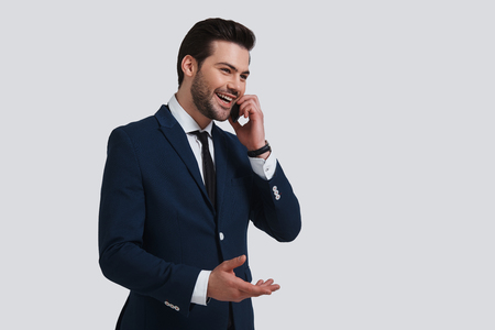 Important talk. Good looking young man in full suit talking on his smart phone and smiling while standing against grey background