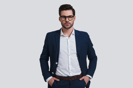 Confident in his style. Handsome young man in full suit keeping hands in pockets and looking at camera while standing against grey background Banque d'images