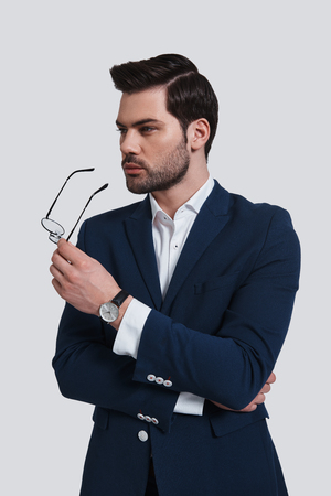 Confident business expert. Handsome young man in full suit holding an eyewear and looking away while standing against grey background