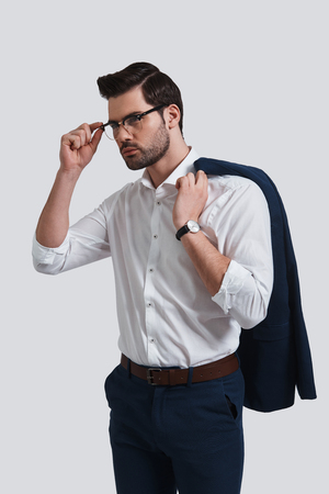 Young and successful. Good looking young man in full suit adjusting his eyewear and looking away while standing against grey background
