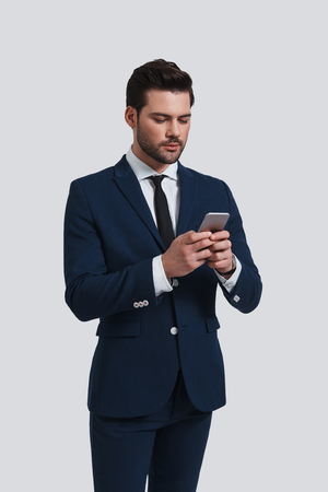 Important business message. Good looking young man in full suit using his smart phone while standing against grey background
