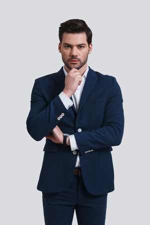 Thoughtful businessman. Handsome young man in full suit keeping hand on chin and looking at camera while standing against grey background