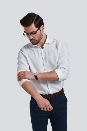 Paying attention to every detail. Good looking young man in formalwear adjusting his sleeve while standing against grey background