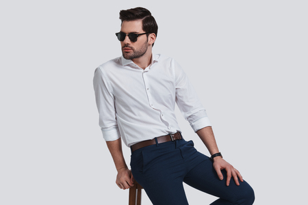 Totally handsome. Good looking young man in eyewear looking away while sitting against grey background