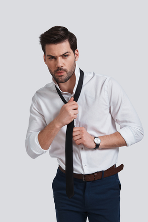 Taking his necktie off.  Tired young man looking at camera and taking on his necktie while standing against grey background