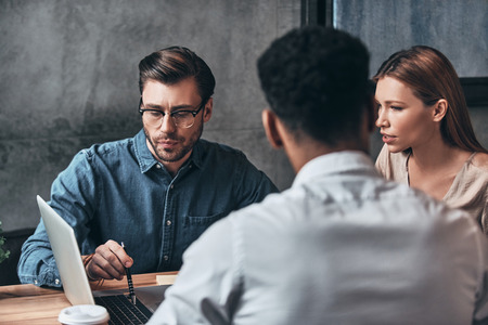 Quick business talk. Group of young confident business people discussing something while spending time in the office Stock Photo - 97955099