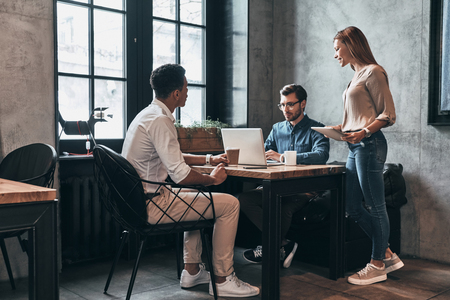 Friendly business chatter. Young modern people in smart casual wear talking while spending time in the office Stock Photo