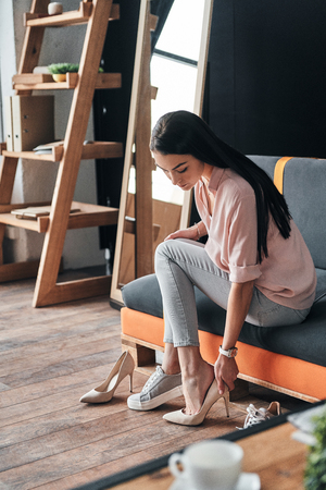 Perfect shoes. Thoughtful young woman trying on elegant shoes with high heels while sitting in the shoe store Stock Photo