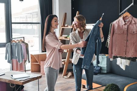 Was denkst du über diesen? Schöne junge Frau, die hilft, Kleidung zu ihrem Kunden beim Arbeiten in der Modeboutique zu wählen Standard-Bild