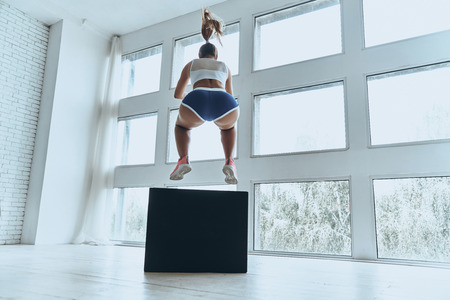 Long jump. Rear view of young woman in sport clothing jumping while exercising in the gym Stock fotó