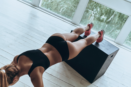 Working hard to be the best. Top view of young woman in sport clothing keeping plank position while exercising in the gym