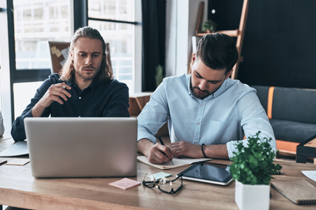 Searching for right decision. Two young modern men in smart casual wear working together while sitting in the creative office Imagens