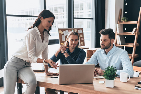 Creative business team. Young modern woman in smart casual wear pointing at laptop while working together with coworkers in the office Imagens