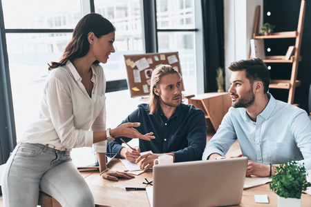 Discussing business issues. Young modern colleagues in smart casual wear working together and smiling while spending time in the office Imagens