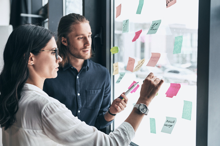 Another good idea. Two young colleagues in smart casual wear using adhesive notes on the window while working together in the office