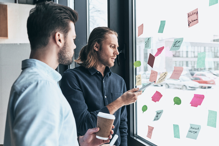 Planning the next step. Two young colleagues in smart casual wear using adhesive notes on the window while working together in the office Imagens