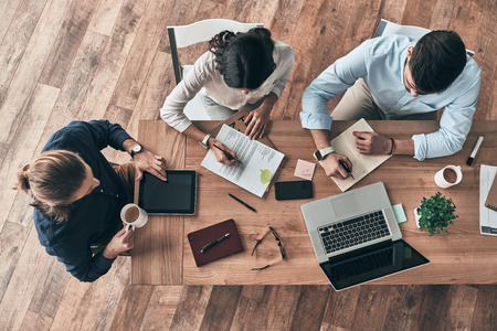 Paying attention to every detail. Top view of young modern colleagues in smart casual wear working together while spending time in the office Imagens