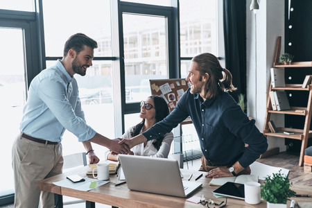 New business partners. Young modern colleagues in smart casual wear shaking hands and smiling while sitting in the creative office
