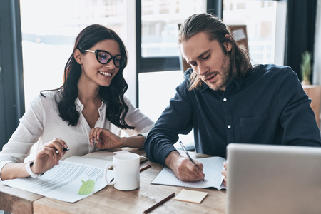 Confident and successful team. Two young modern people in smart casual wear writing something down and smiling while sitting in the creative office