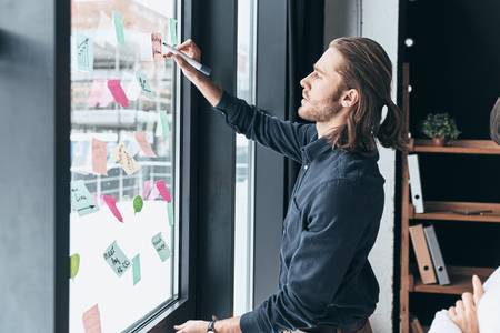 Working through some concepts. Modern young man in smart casual wear using adhesive notes on the window while working with his colleague in the office