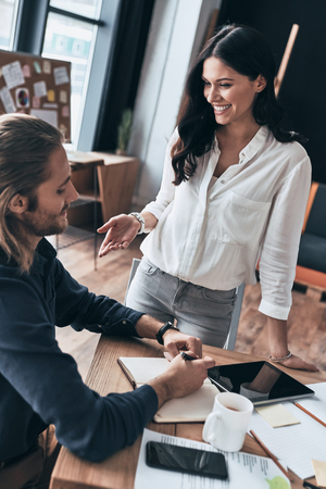Happy to work together. Top view of young modern woman in smart casual wear gesturing and smiling while working together with colleague in the office