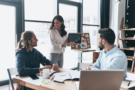 Interesting presentation. Modern young woman pointing copy space at digital tablet while conducting a business presentation in the office Imagens