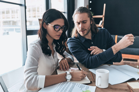Successful professionals. Two young modern people in smart casual wear writing something down while sitting in the creative office Stock Photo