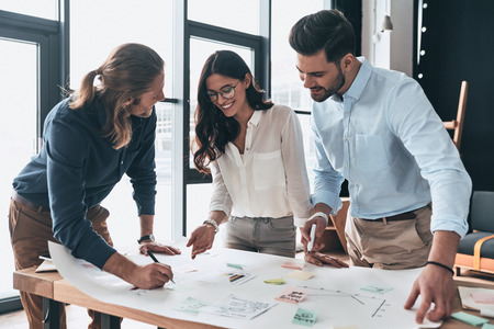 Another project. Group of young confident business people working together and smiling while man writing on blueprint in the office Stock Photo